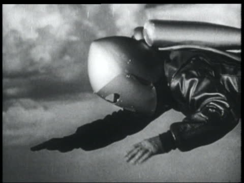 b/w 1952 close up tracking shot man with jet pack on back + helmet flying + turning knob on chest - 1952 stock videos & royalty-free footage