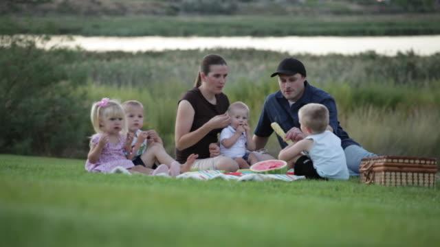 vídeos de stock e filmes b-roll de a close up tracking shot of a family of six having a picnic by a lake while the sun is setting. - família com quatro filhos