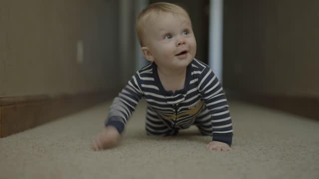 close up tracking shot of approaching baby boy crawling on corridor floor / cedar hills, utah, united states - crawling stock videos & royalty-free footage