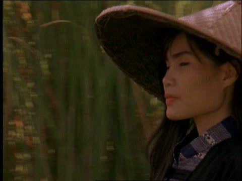 stockvideo's en b-roll-footage met close up tracking shot of asian woman in straw hat walking in field, she turns to camera / thailand - strohoed