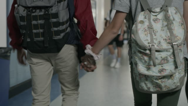 stockvideo's en b-roll-footage met close up tracking shot of boy and girl holding hands and walking in school corridor / provo, utah, united states - lockerkast