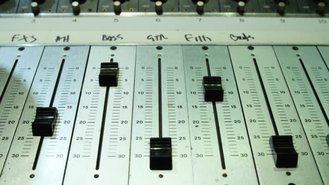 Close up tracking shot of channel faders on a sound mixing desk
