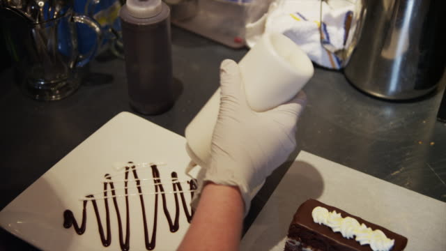 vídeos de stock, filmes e b-roll de close up tracking shot of chef preparing dessert on plate / orem, utah, united states,  - luvas