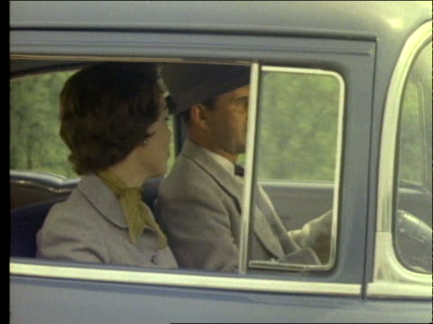 1955 close up tracking shot of couple driving car - paar mittleren alters stock-videos und b-roll-filmmaterial