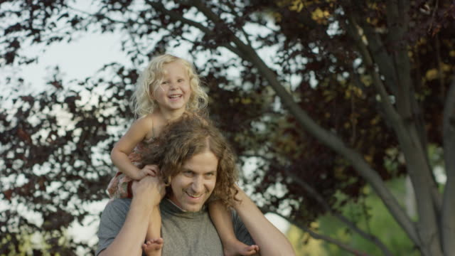 close up tracking shot of father carrying daughter on shoulders / orem, utah, united states - orem utah stock videos & royalty-free footage