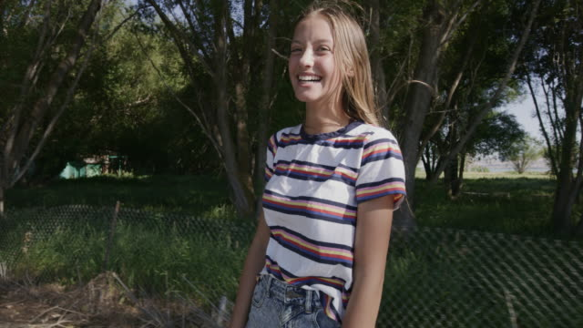 stockvideo's en b-roll-footage met close up tracking shot of happy girl riding skateboard looking at camera and gesturing peace / saratoga springs, utah, united states - vredesteken handgebaar