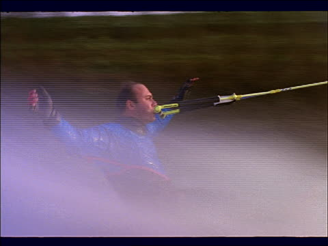 close up tracking shot of man waterskiing barefoot + doing stunts