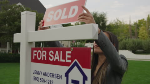 close up tracking shot of realtor placing sold sign on post of house for sale / pleasant grove, utah, united states - vendor stock videos & royalty-free footage