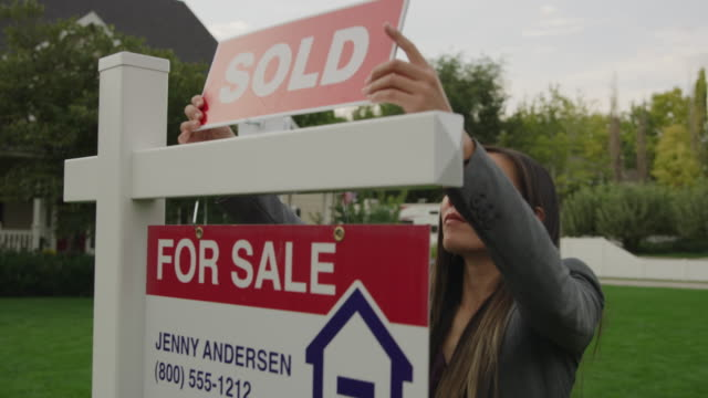 vidéos et rushes de close up tracking shot of realtor placing sold sign on post of house for sale / pleasant grove, utah, united states - vendre