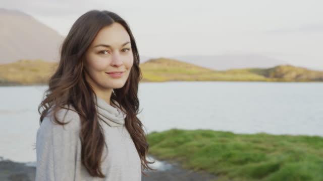 vidéos et rushes de close up tracking shot of smiling woman walking near river / borgarnes, iceland - cheveux bruns