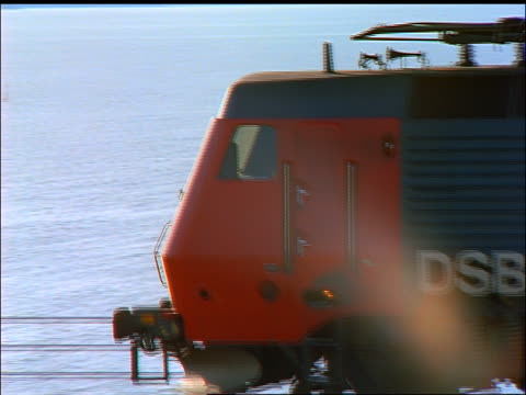 aerial close up tracking shot of train / zoom out to freight train carrying cars on bridge / zoom in to cars / nyborg, fyn - rail freight stock videos and b-roll footage