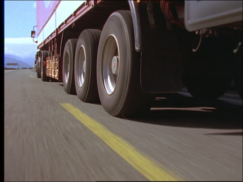 close up tracking shot of wheels on moving tractor trailer truck