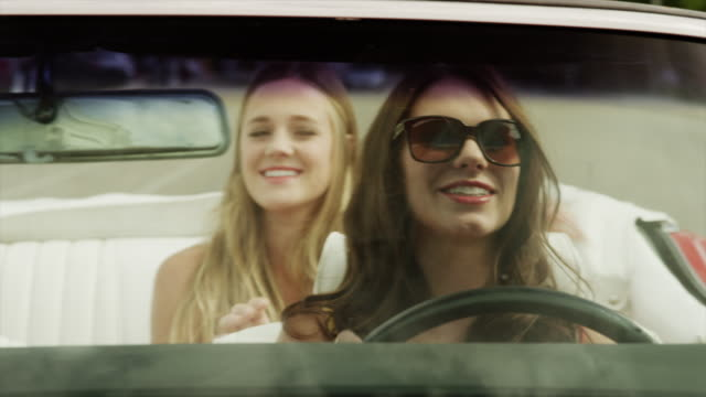 Close up tracking shot of young women driving convertible car / Pleasant Grove, Utah, United States