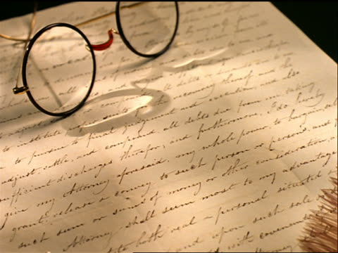 close up tracking shot over eyeglasses + quill sitting on yellowing hand written letter