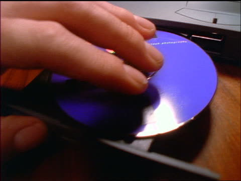 close up tracking shot over man's hands placing cd rom into drive of laptop to keyboard - 1998 stock videos & royalty-free footage