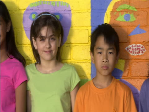 close up tracking shot portait of children standing against brightly painted school wall and smiling at camera/ london, england - 2006 stock videos & royalty-free footage