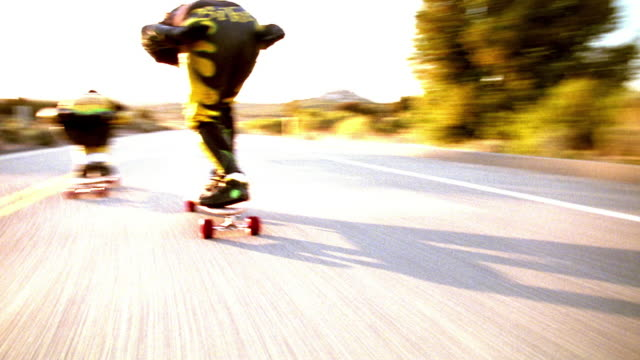 OVEREXPOSED close up tracking shot REAR VIEW two skateboarders speeding on mountain road