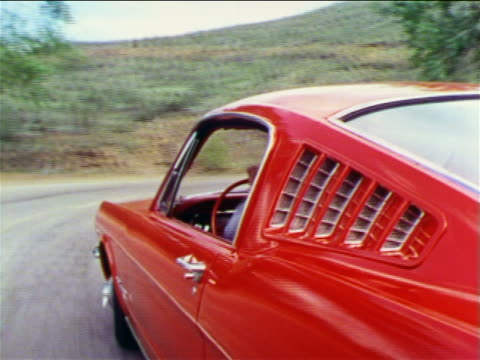 1965 close up tracking shot red Ford Mustang speeding around curve on country road / man's hand driving visible