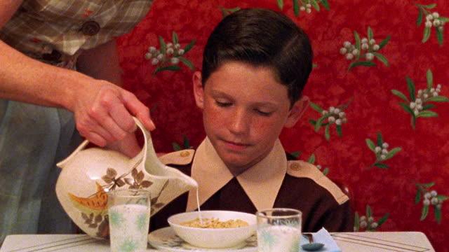 vidéos et rushes de reenactment close up tracking shot reenactment woman's hands pouring milk into children's cereal bowls at kitchen table - 1950