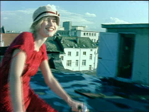 close up tracking shot smiling young blonde woman with hat + dress riding bike on roof of building - sonnenhut stock-videos und b-roll-filmmaterial