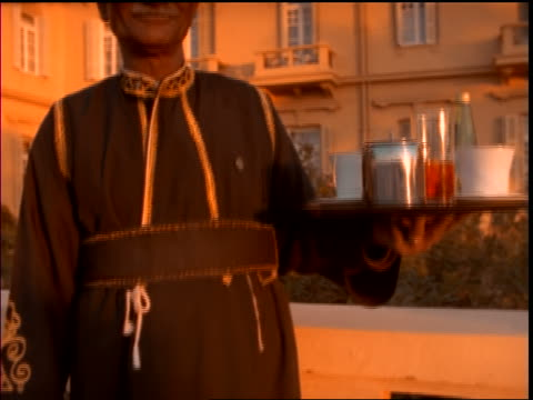 close up tracking shot up of man holding tray with tea + teacups on tray / Egypt