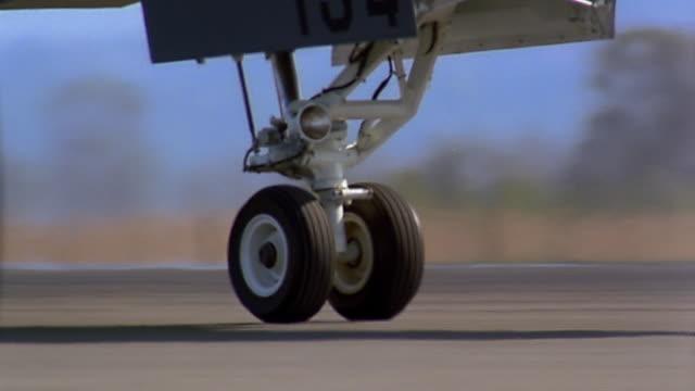 Close up tracking shot wheel of fighter jet moving on runway / tilt up pilot in cockpit