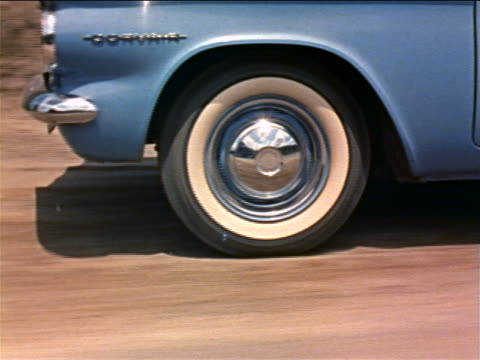 1960 close up tracking shot whitewall tire on corvair driving on rough dirt road / industrial - 1960 stock-videos und b-roll-filmmaterial