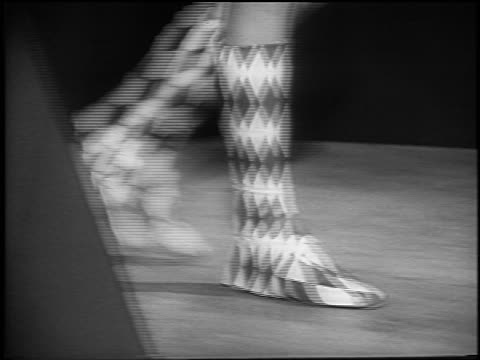 B/W 1965 close up tracking shot woman's feet walking in harlequin boots + turning toward camera / NYC / newsreel