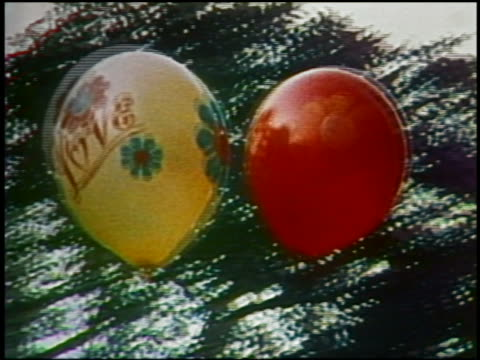 "1975 close up tracking shot yellow balloon with ""love"" written on it next to red balloon - grobkörnig stock-videos und b-roll-filmmaterial"