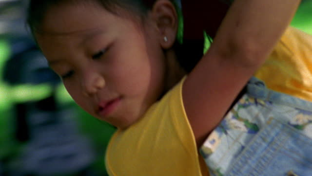 vidéos et rushes de close up tracking shot young asian girl swinging on tire swing attached to tree / florida - balançoire pneu