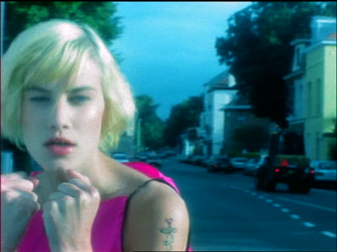 vidéos et rushes de close up tracking shot young blonde woman with pink dress + tattoo on arm on street shadow boxing with camera - 1990 1999