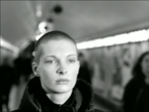 B/W close up tracking shot young woman with shaved head walking in tunnel in subway station / other people in background