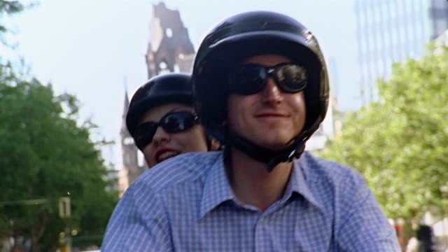 close up tracking shot zoom out man and woman riding vespa / berlin, germany - moped stock videos and b-roll footage