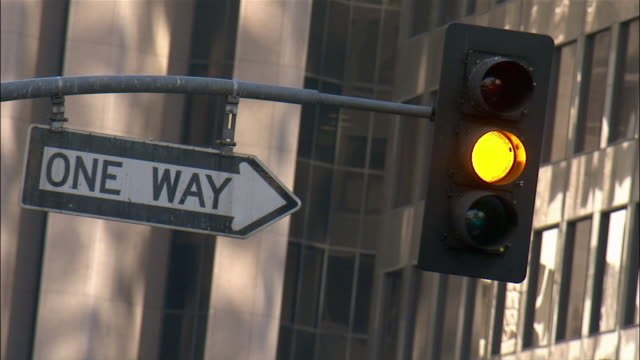 "Close up traffic light changing from green to red with ""One Way"" sign/ Los Angeles, California"