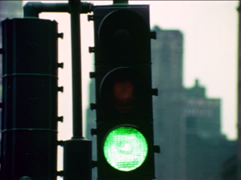 1965 close up traffic light changing from red to yellow to green / educational