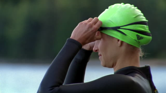 close up triathlete in wetsuit putting on goggles and warming-up on shore of lake - swimming goggles stock videos & royalty-free footage