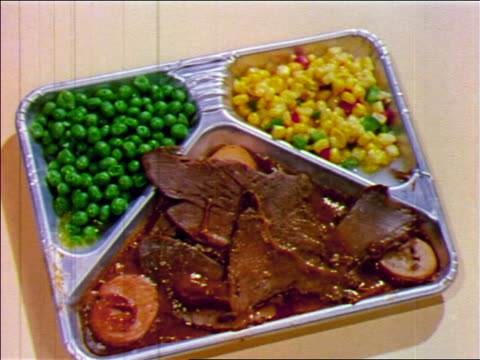 1955 close up tv dinner with beef, potatoes, peas + corn / industrial - インスタント食品点の映像素材/bロール
