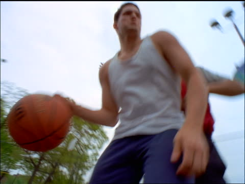 close up two Black + Caucasian men playing basketball outdoors / one shoots + scores