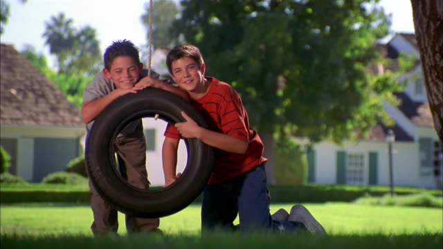 close up two boys looking at cam behind tire swing - tire swing stock videos & royalty-free footage
