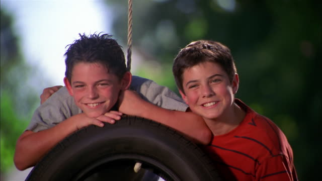 close up two boys smiling at cam behind tire swing in yard / boy teasing and rubbing other boy's head - tire swing stock videos & royalty-free footage