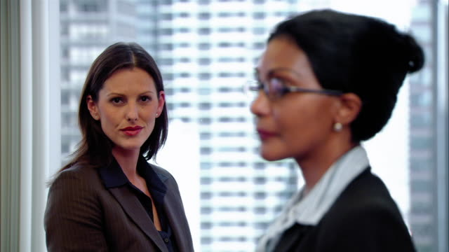 close up two business women standing against window and looking at camera/ new york, new york - formal businesswear stock videos & royalty-free footage