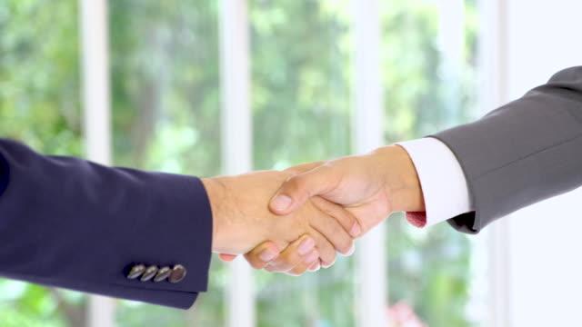 Schließen Sie sich zwei Geschäftsmann aufstehen und händedruck beschäftigen sich mit Geschäftsvereinbarung im Tagungsraum