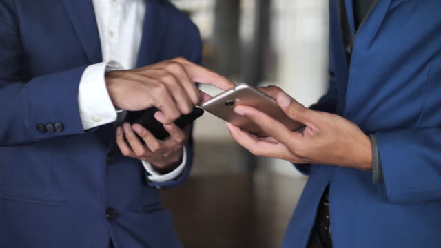 Close up Two businessman using smart phone, Slow motion