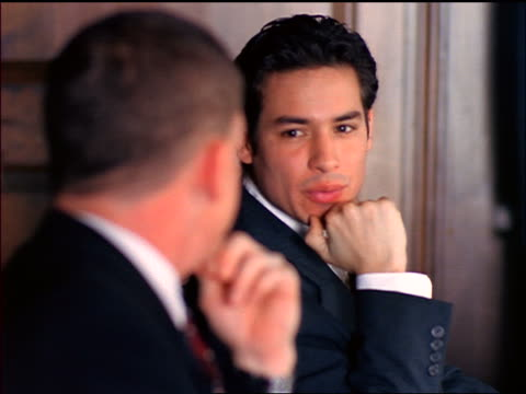 close up two businessmen talking at table / tv monitor barely visible in background - formal businesswear stock videos & royalty-free footage