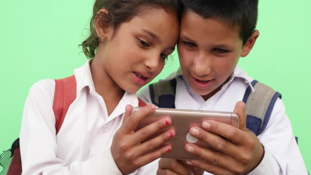 Close up, Two kids, boy and girl, sharing and enjoying a smart phone mobile device in school uniform