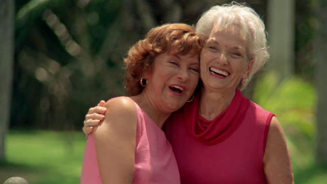 Close up two mature women hugging and smiling at CAM