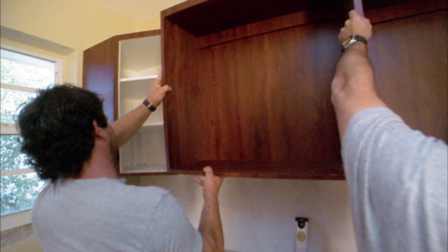 vídeos de stock, filmes e b-roll de close up two men installing cabinet in kitchen - cabinet