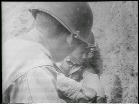 vidéos et rushes de close up two soldiers in foxhole with eyes closed during h-bomb explosion / yucca flats, nevada - 1952