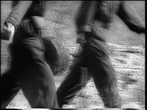 b/w 1961 close up pan two soldiers unrolling barbed wire in construction of berlin wall / newsreel - wall building feature stock videos & royalty-free footage