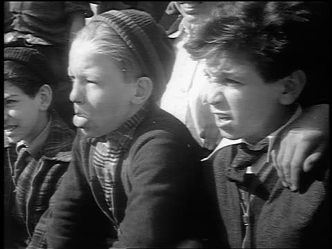 B/W 1941 close up two young boys sitting in baseball audience watching / one sticks out tongue / newsreel